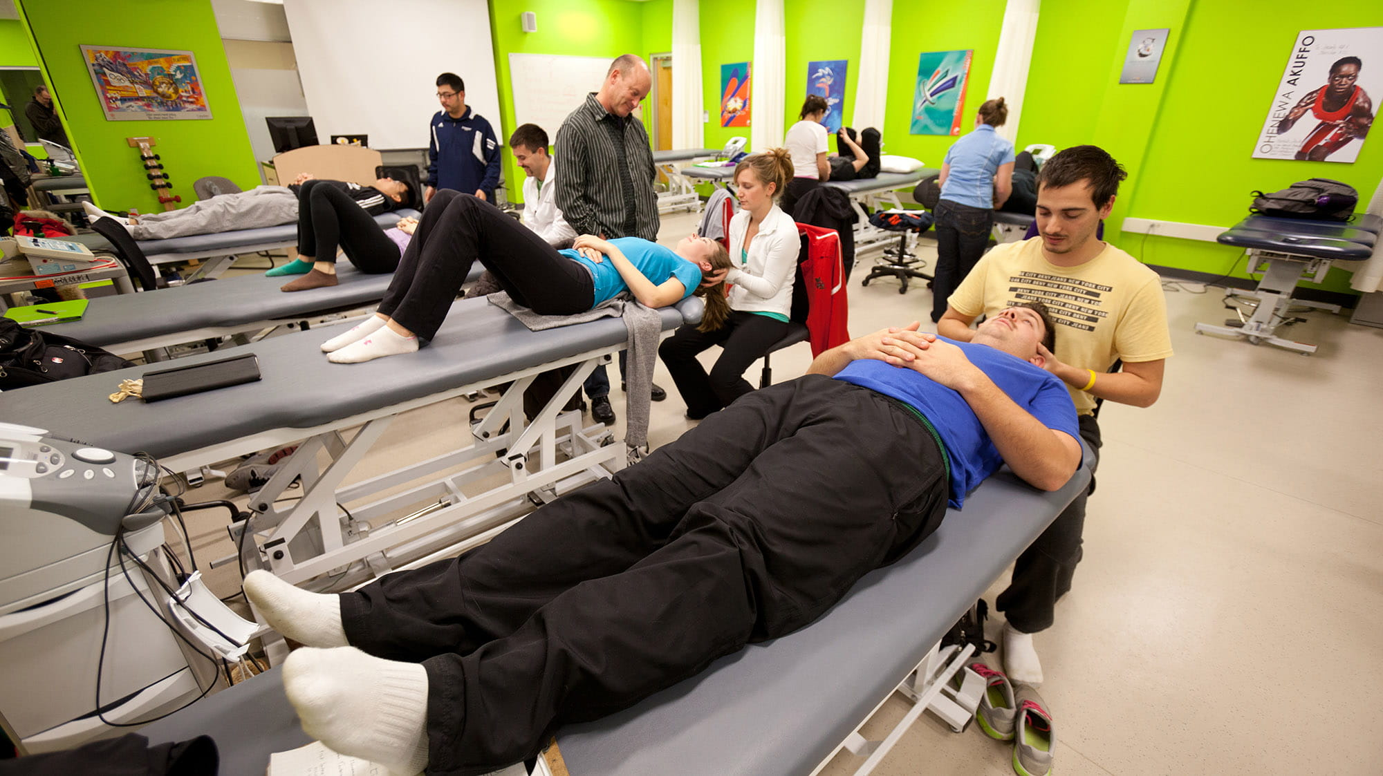 Athletic therapy room filled with therapy tables and students practicing on one another