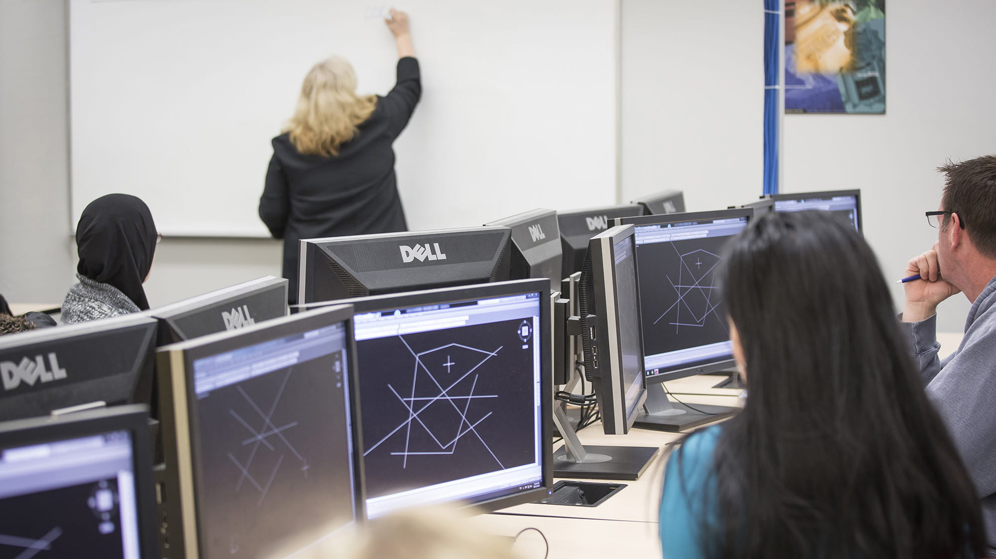 Students with computers in a CAD lab watching a teacher write on a white board