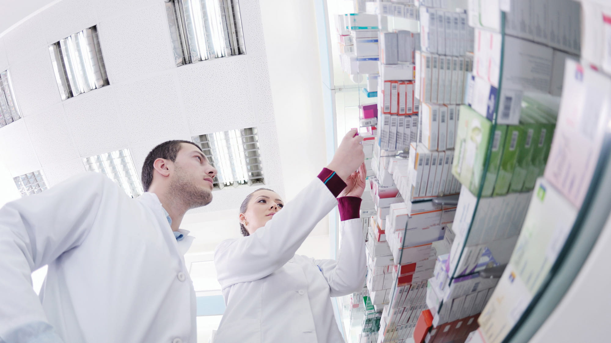 Two pharmacy students in lab coats looking at shelves of pharmaceutical supplies