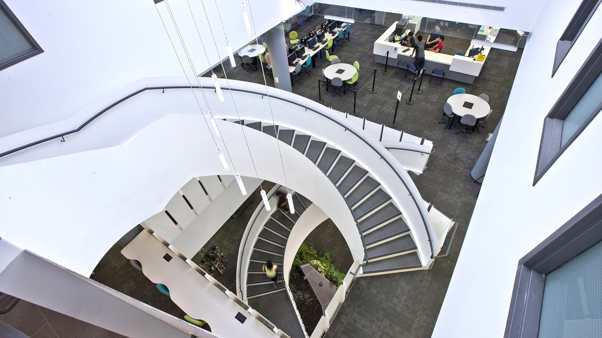 The bright white spiral stairs at the library as seen from the top
