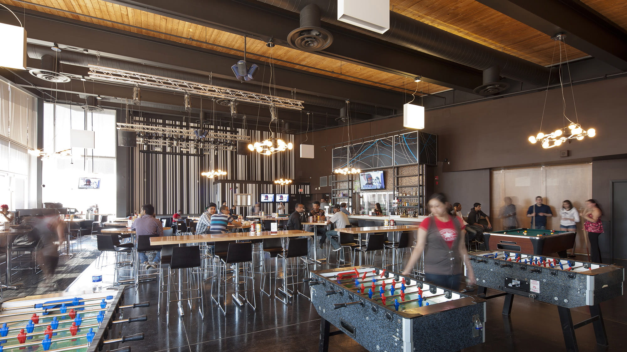 A pub filled with tables, chairs, foosball tables and students chatting