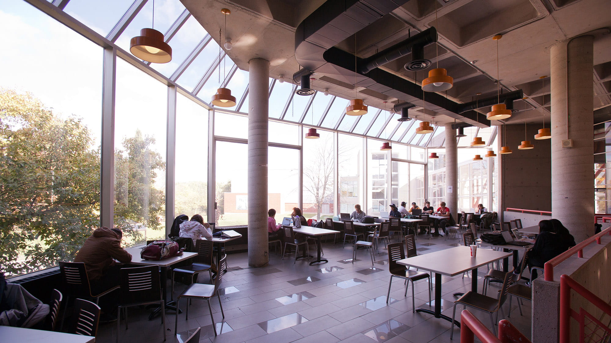 Students eating at tables in the cafeteria beside a wall of large bright windows