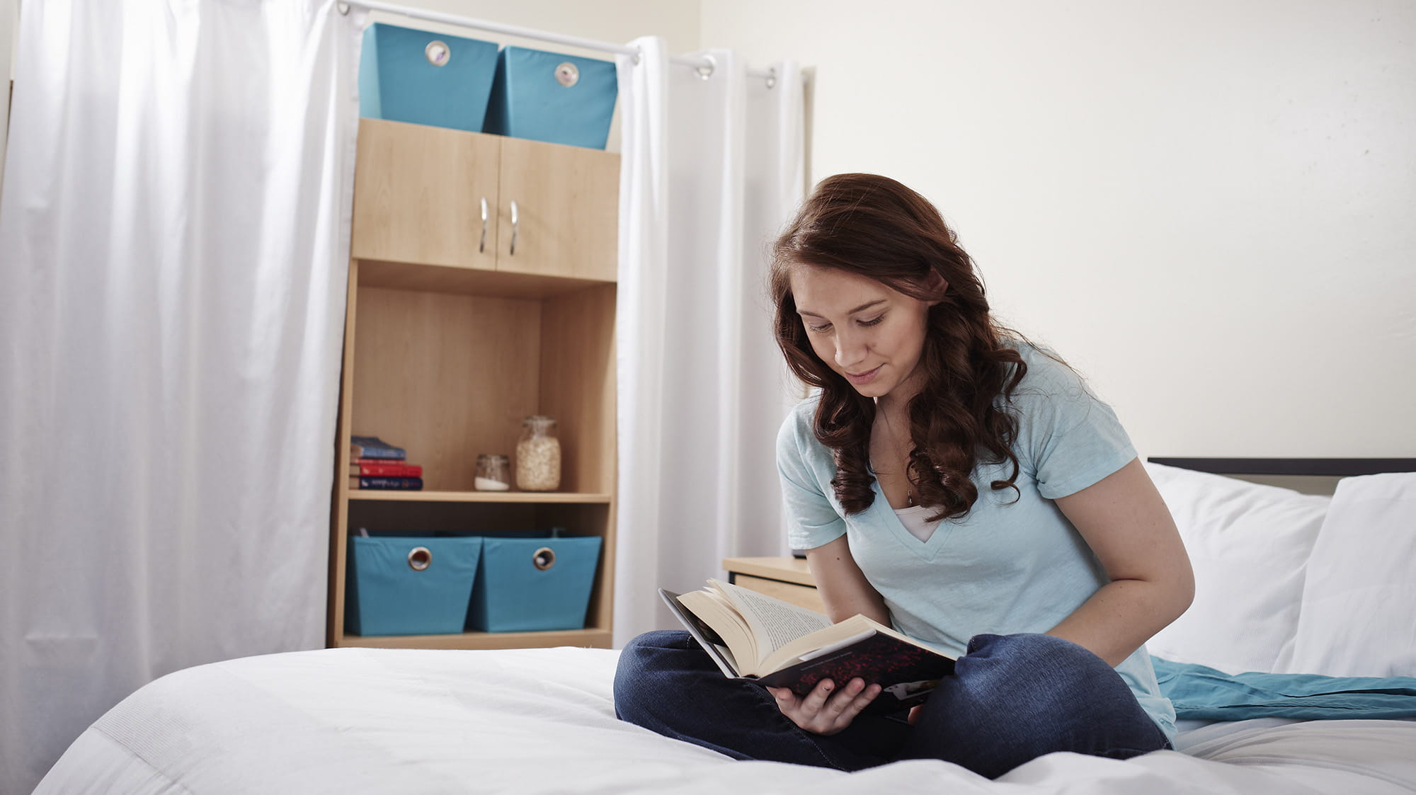 A girl reading a book on her bed in her residence room