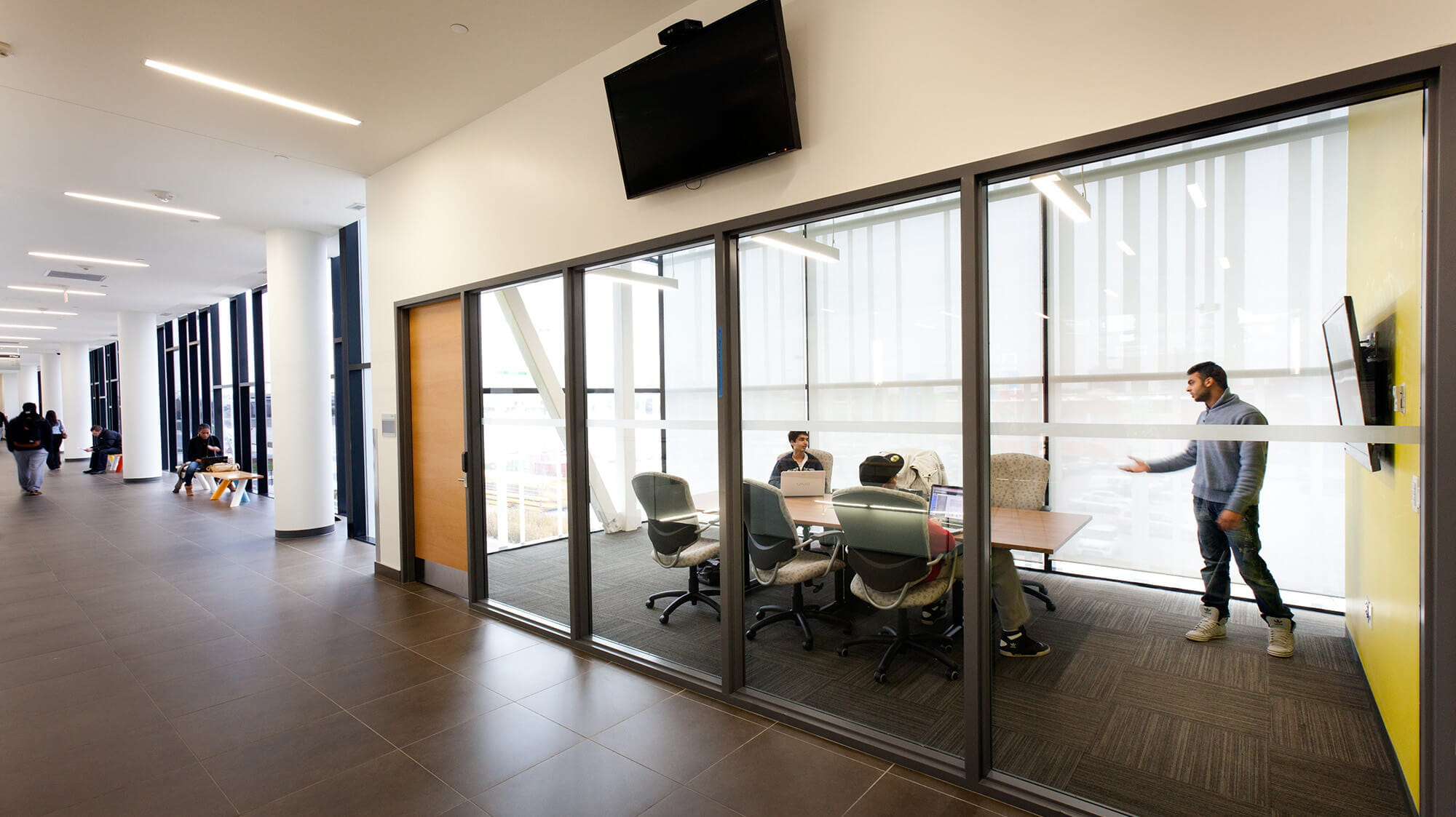 A hallway looking into a glass-walled group study room with a table and students inside.