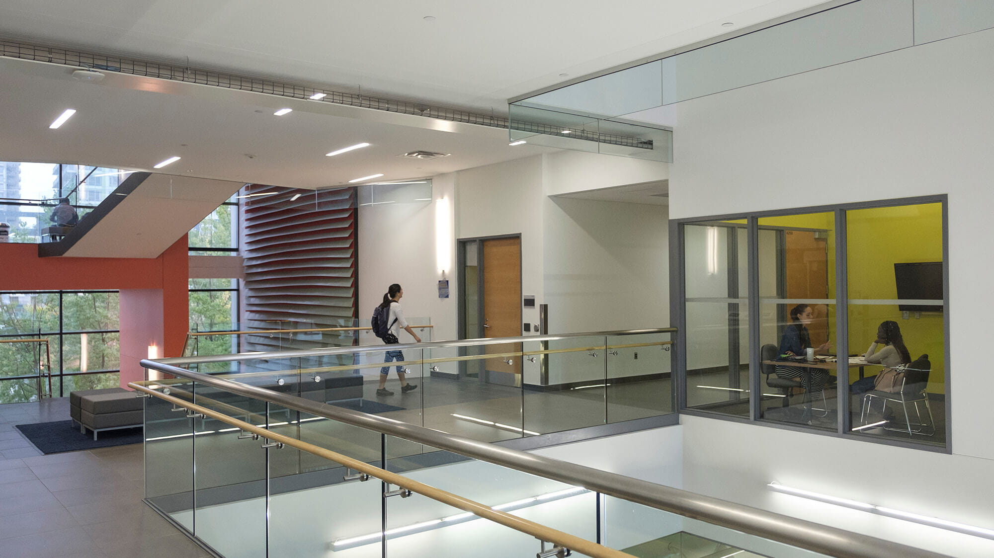A hallway with stairs and a view inside a glass-walled Group Study Room