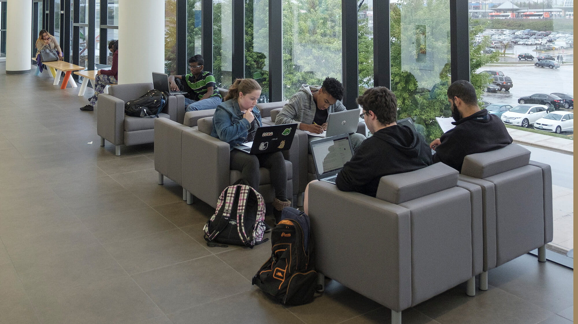 Students with latops sitting in comfortable chairs in a hallway with tall bright windows