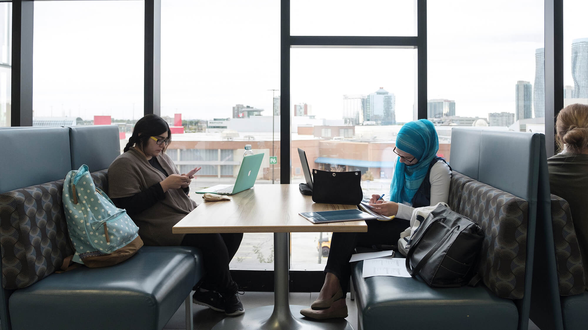 Two students sitting across from each other and studying in a booth with bright tall windows