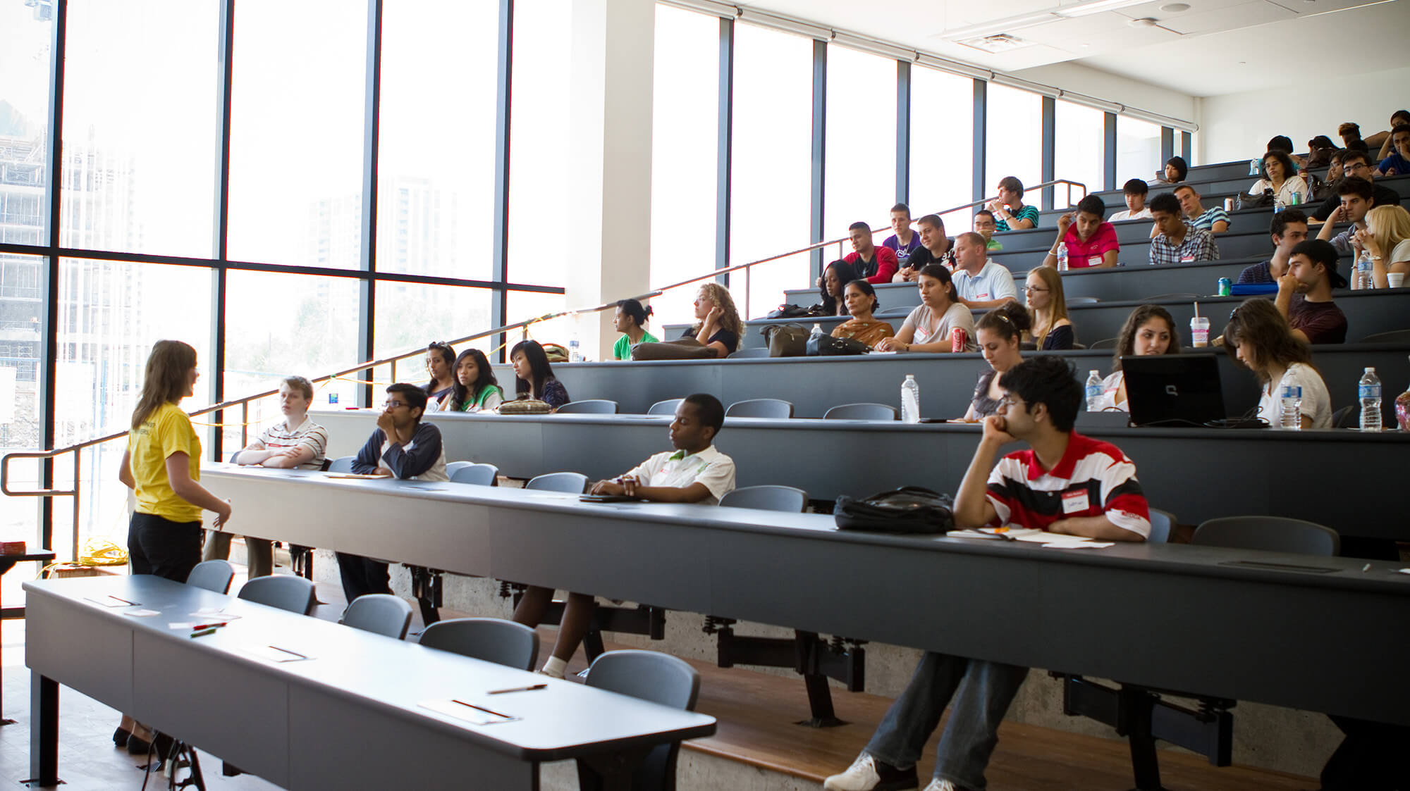 Many students and a teacher in a tiered lecture hall with a wall of windows