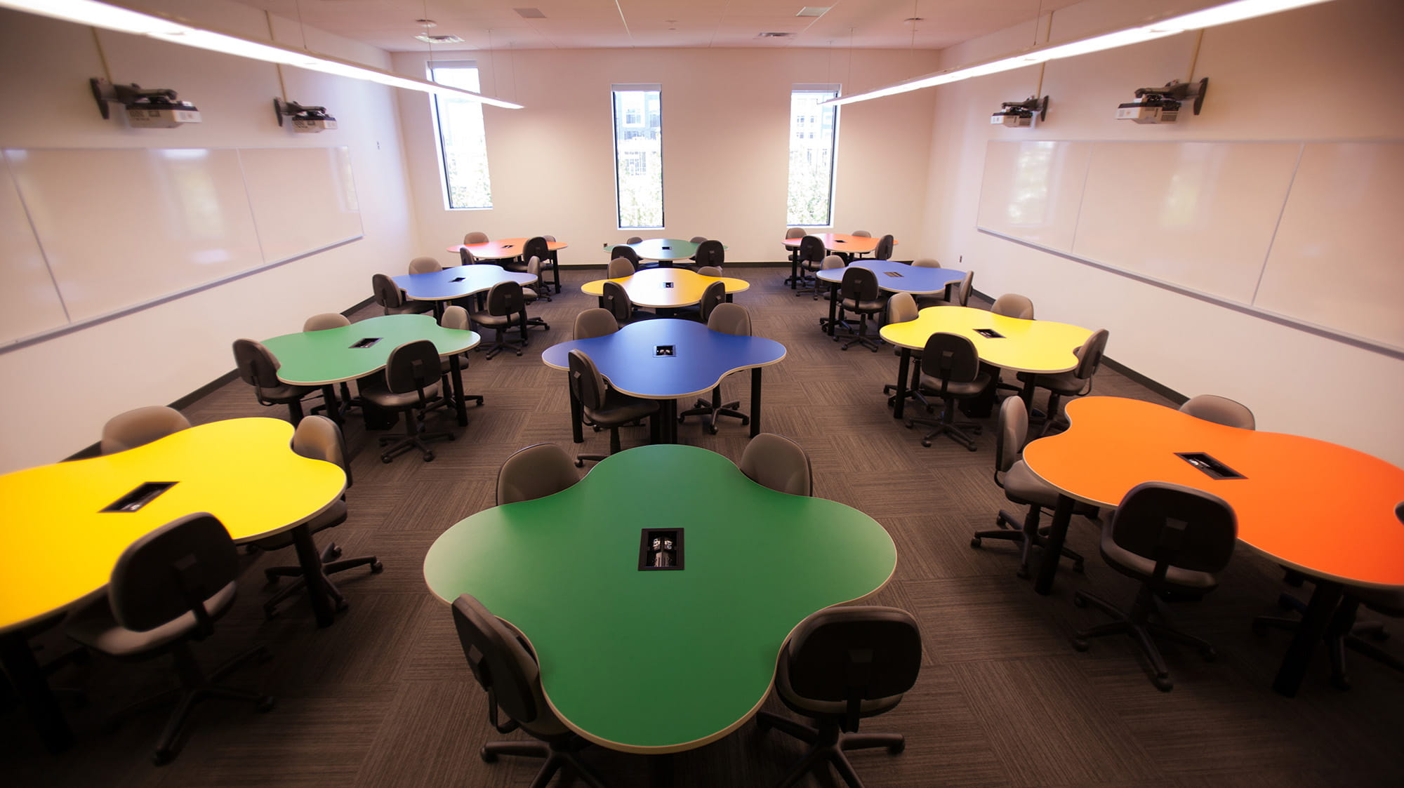 A room with multicoloured amoeba-shaped tables.