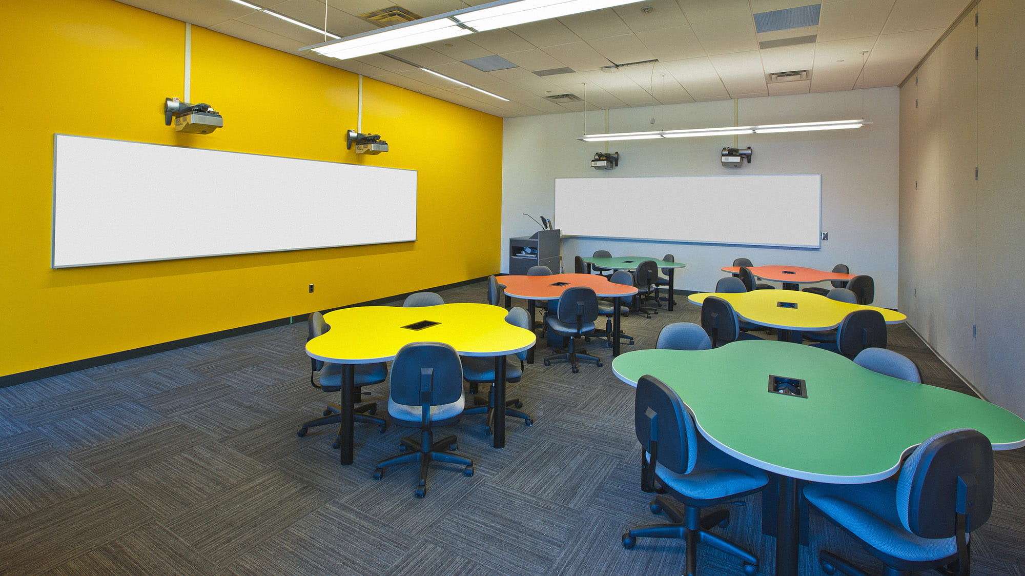 A classroom with a yellow wall, filled with multicoloured amoeba-shaped tables.