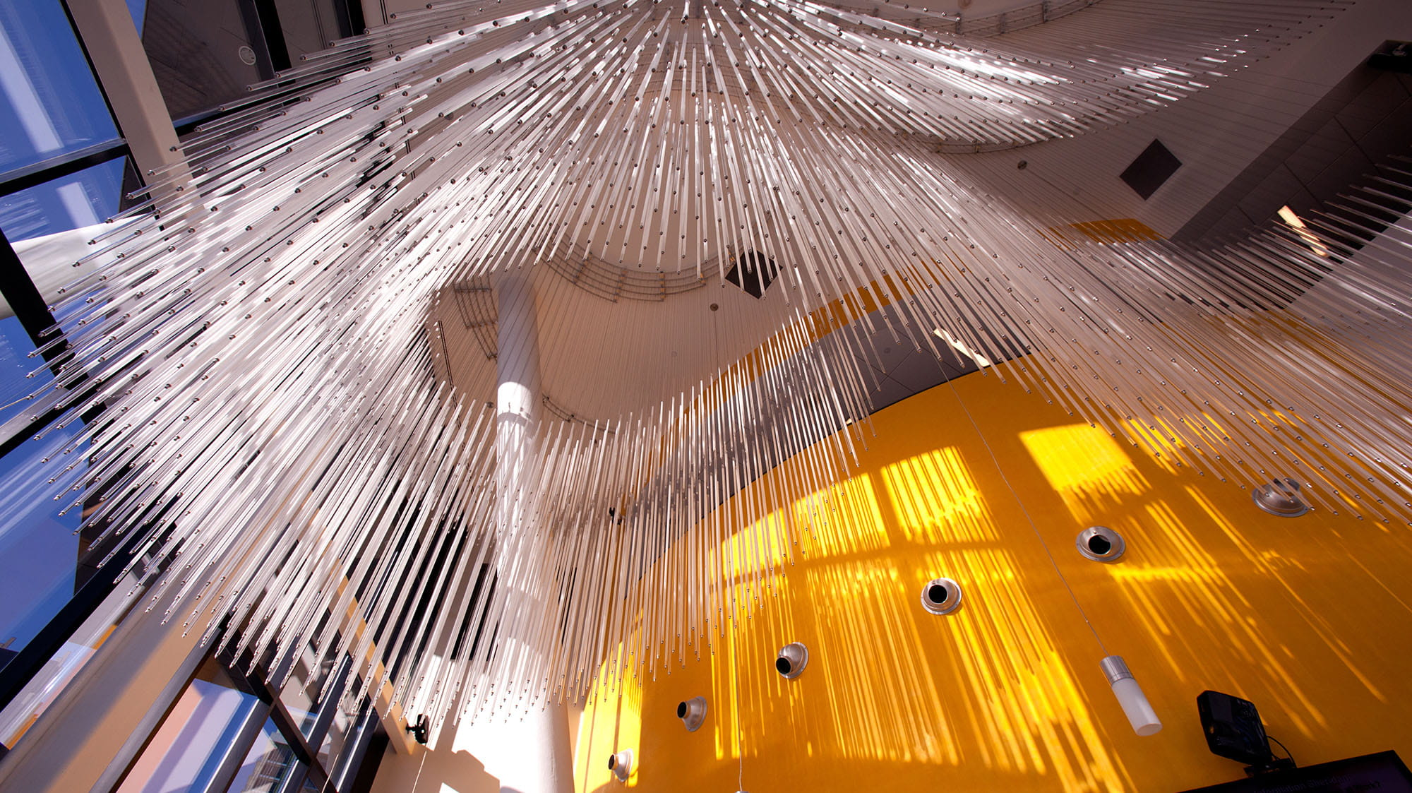 The view looking up at a sculpture of long strands of glass hanging from the ceiling
