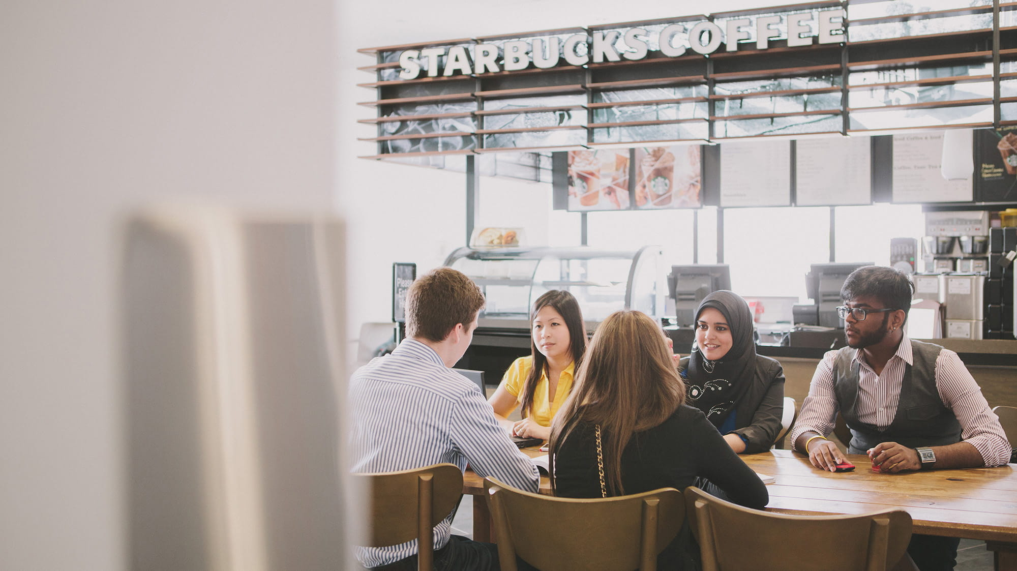 A group of students sitting at a table at Starbucks.