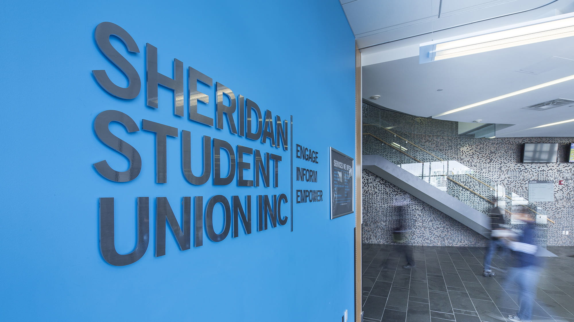 A large blue Sheridan Student Union sign in a hallway