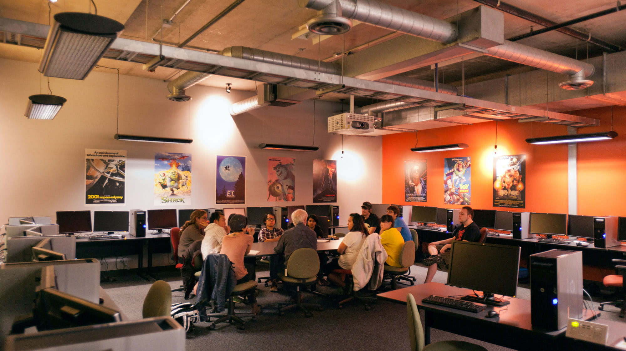 An instructor talking to a group of students in a room with lots of computers and posters of animated films on the walls