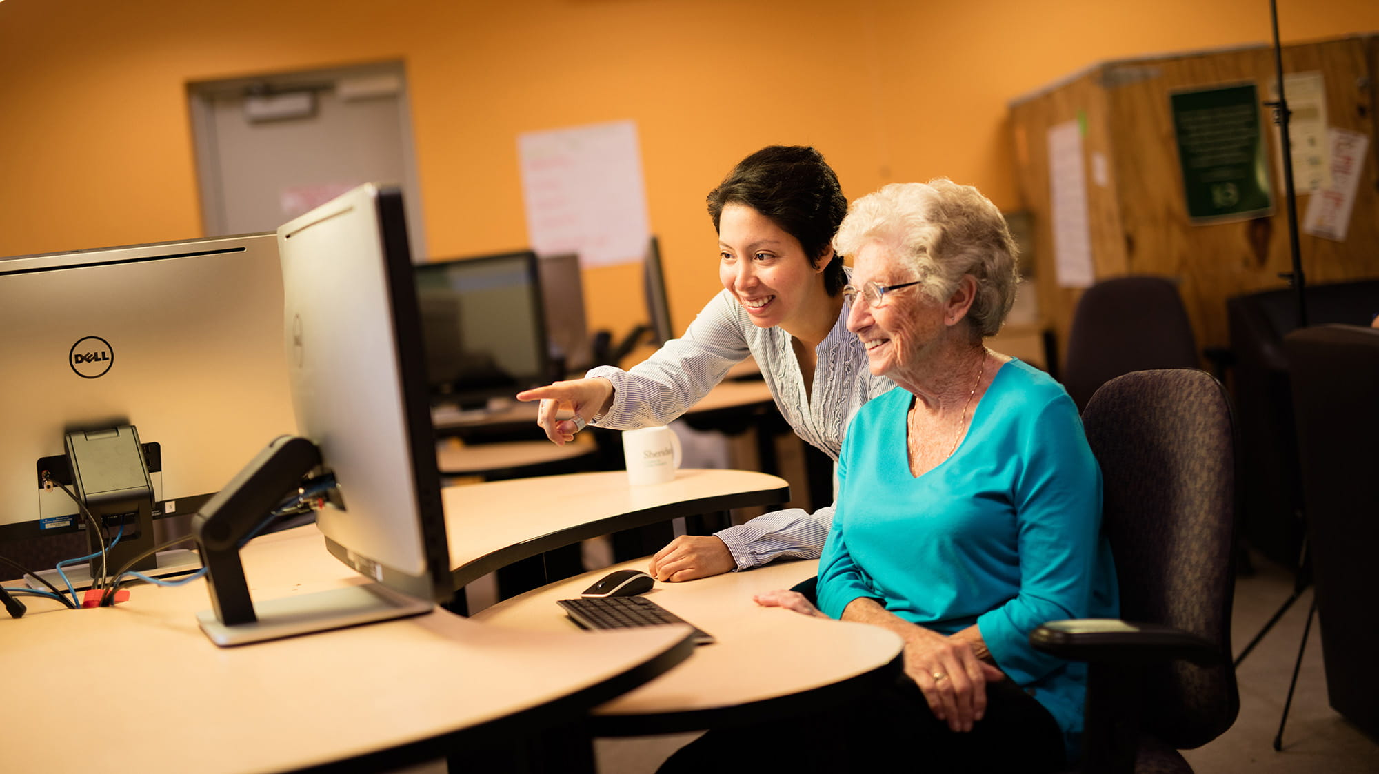 A student helping an older woman work on a computer