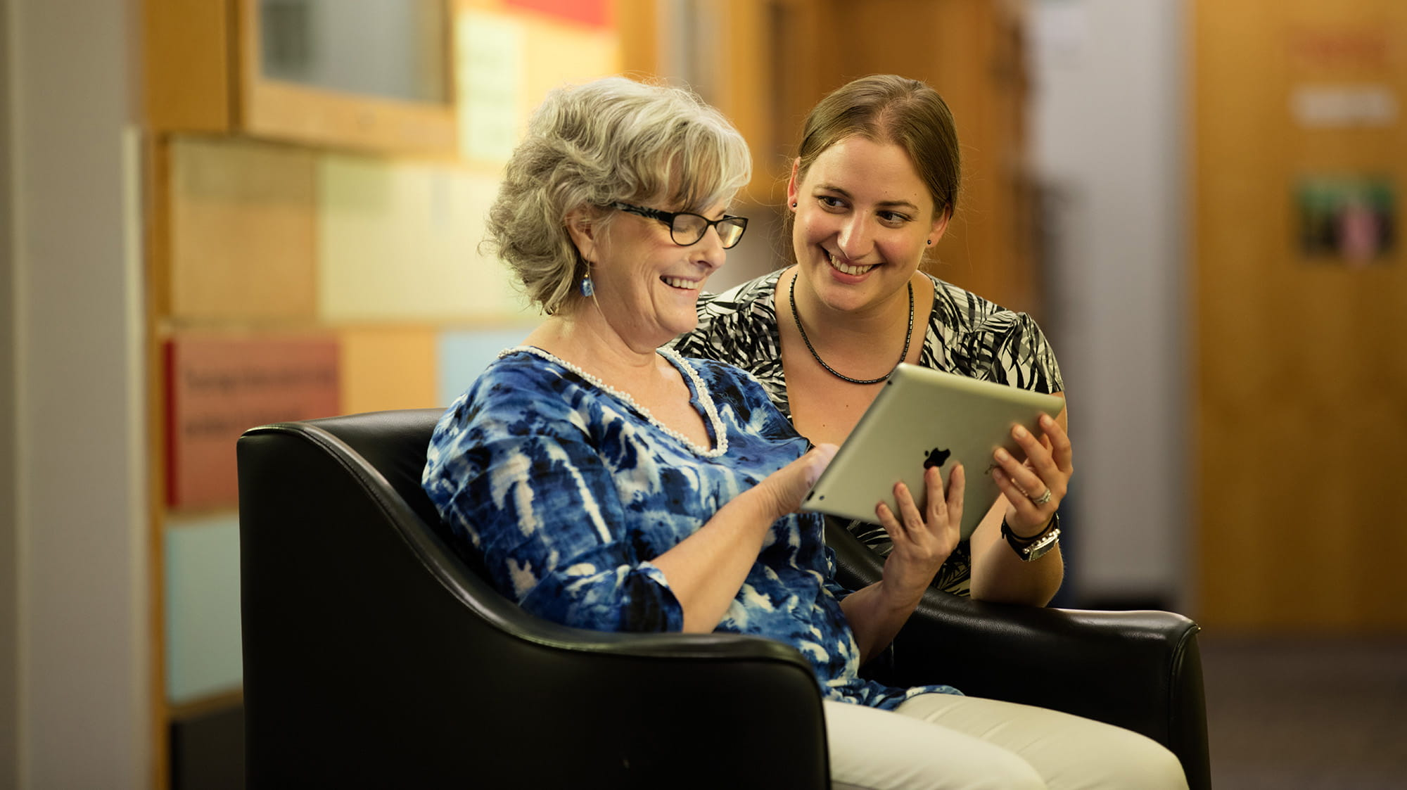 A student helping an older woman use a tablet
