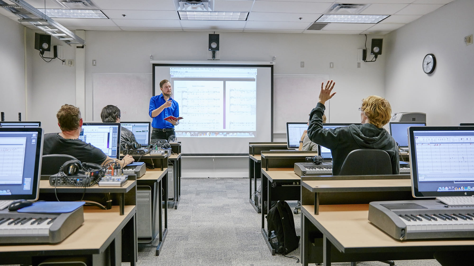 An instructor talking to students who are at computers with music keyboards