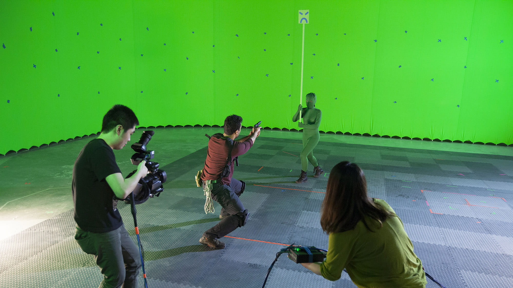 Students filming two people in a large room with green walls