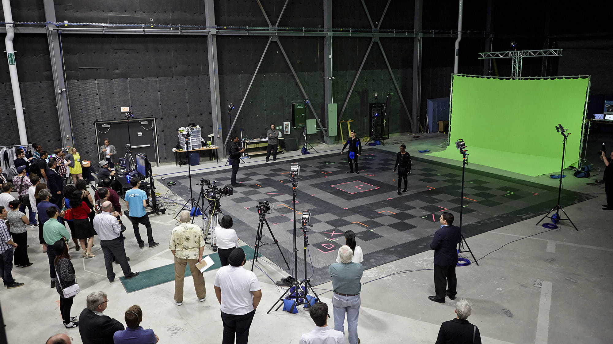 A large studio filled with a production crew, cameras, lights, and a green screen