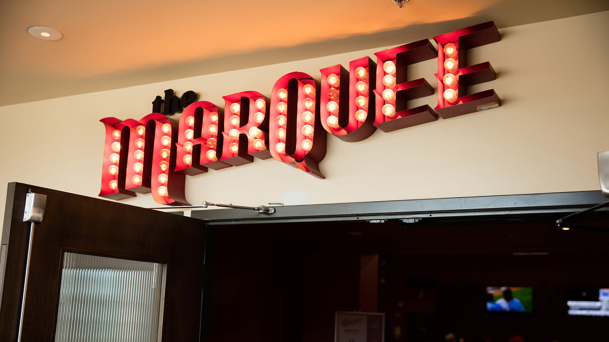 The Marquee sign with red letters and lights over the door to the pub