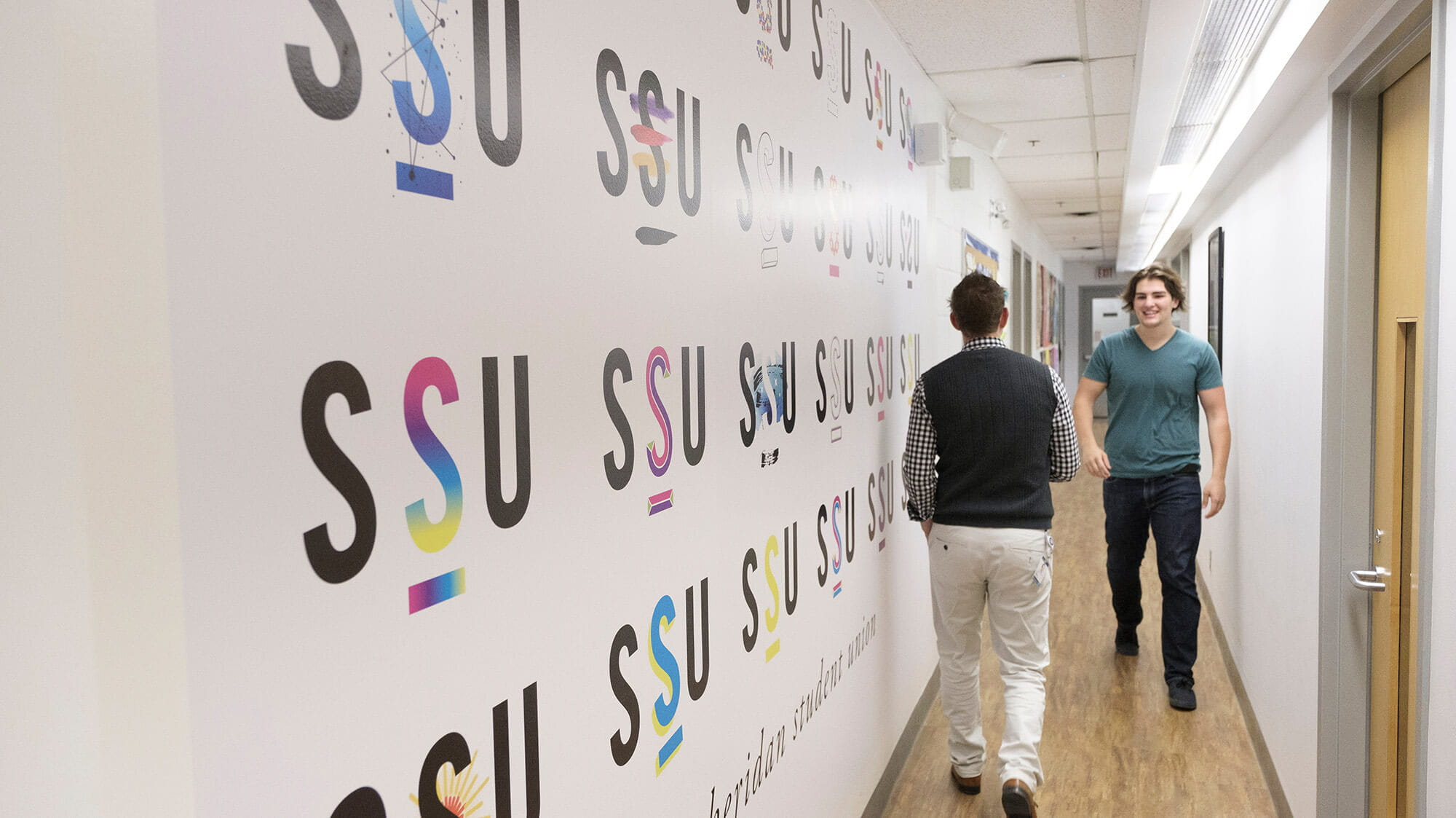 Students walking down a hallway with the SSU logo on the wall