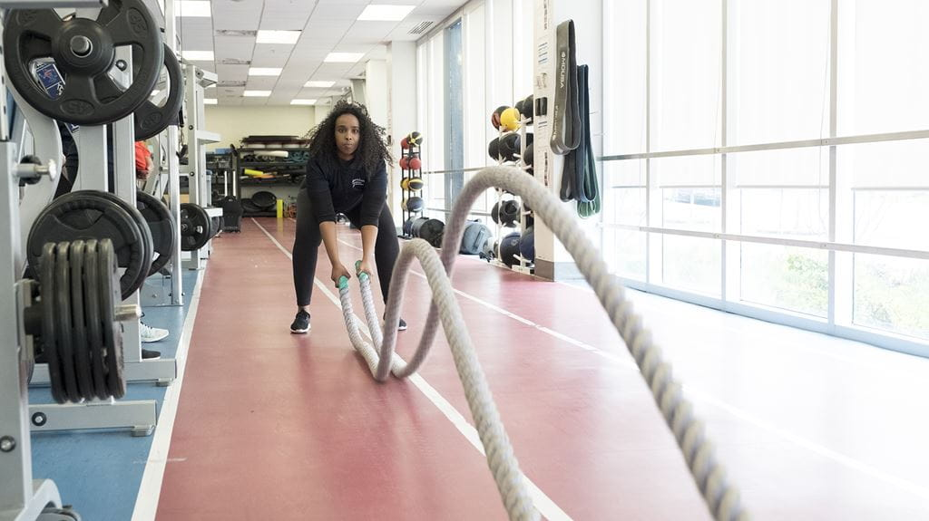 An athlete doing battle rope exercises in Sheridan's Strength and Conditioning Facility