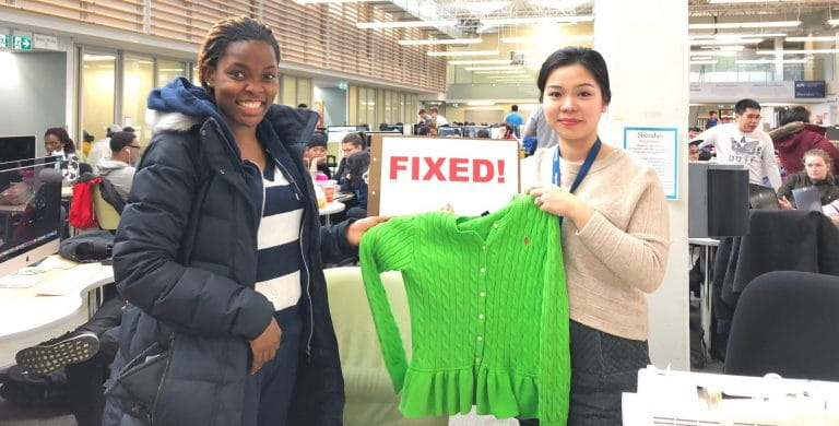 Two people holding up a sweater that was fixed at a Sheridan Repair cafe