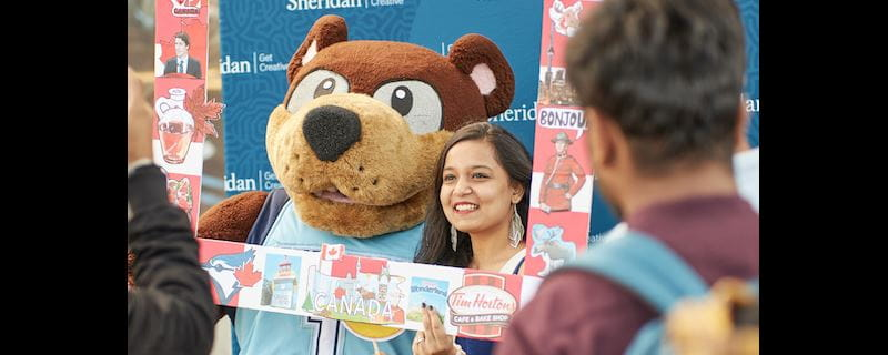 A female student poses for a photo in a Canada-themed frame with Sheridan College mascot Bruno the Bruin