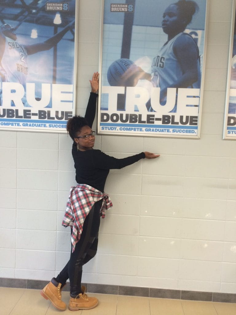 Shylanda Saunders posing in front of her Double-Blue poster
