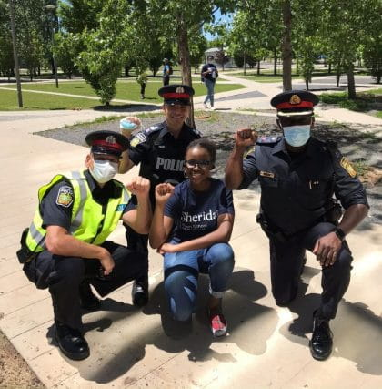 Stephanie Garrick (centre) kneeling with members of the Peel Regional Police at the Sheridan Black Students Association solidarity march