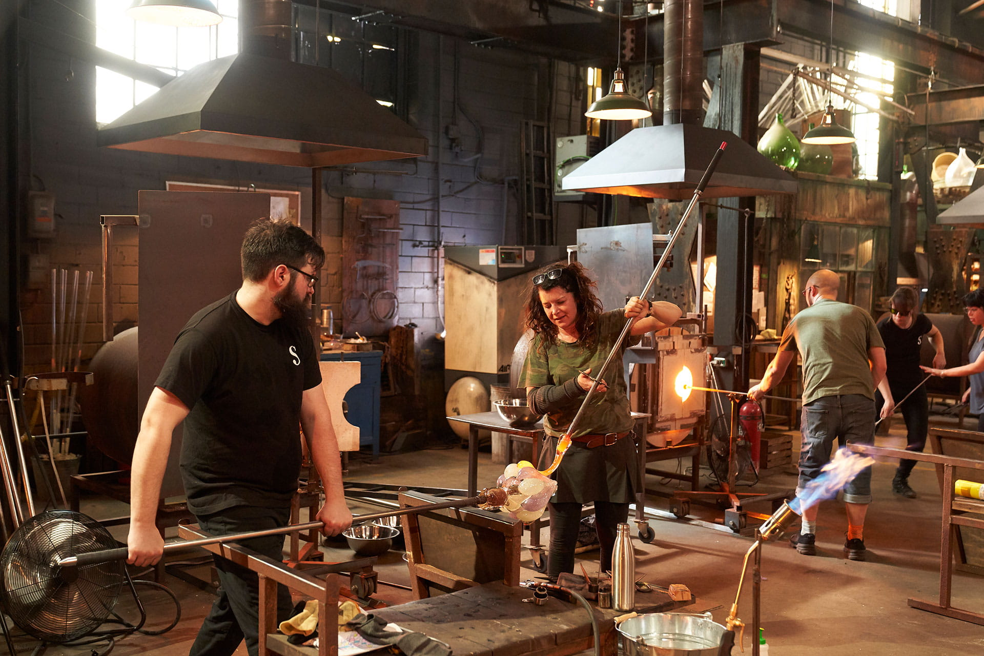 Glassblowers working with glass on the set of Netflix's Blown Away
