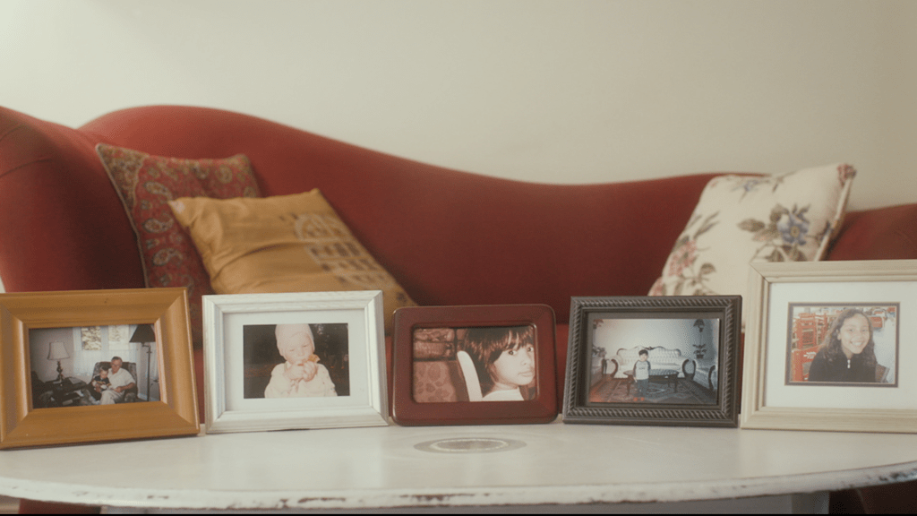 Framed photos on a table - still from the short film On the Fence