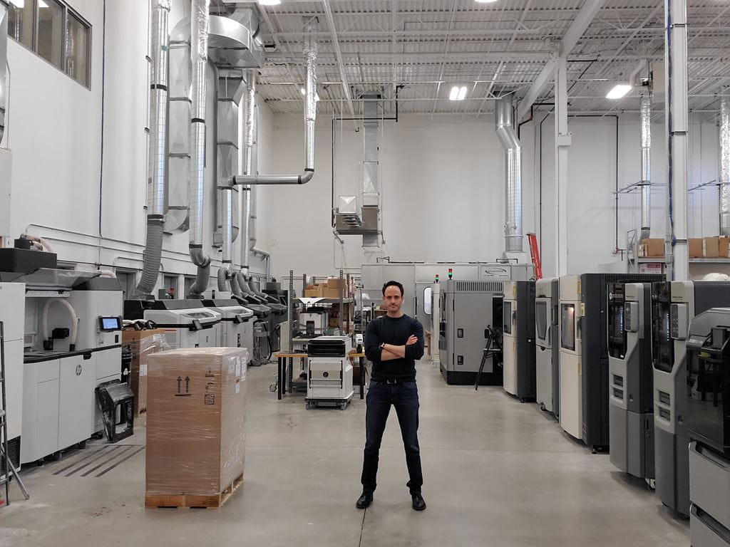 Eyal Geiger standing in front of additive manufacturing equipment.