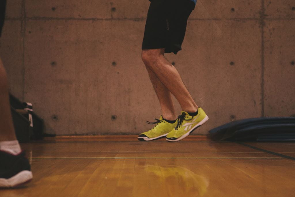 Person with yellow athletic running shoes jumping off the ground
