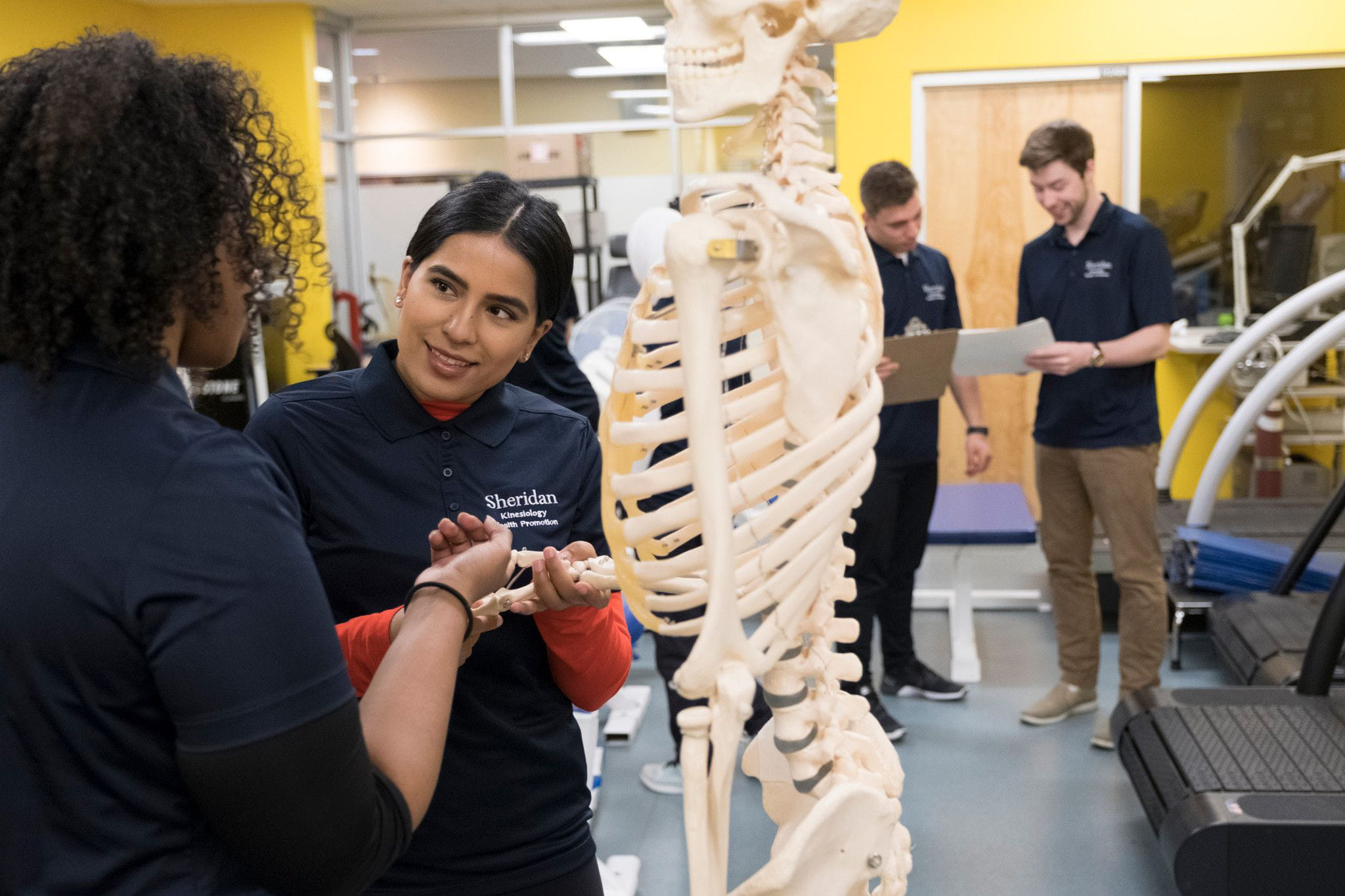 Kinesiology students speaking next to a skeleton in a classroom