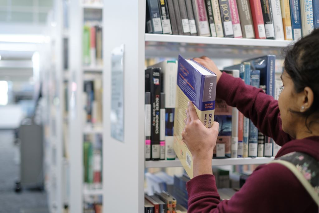 Student putting a book back on the shelf at Sheridan's Library