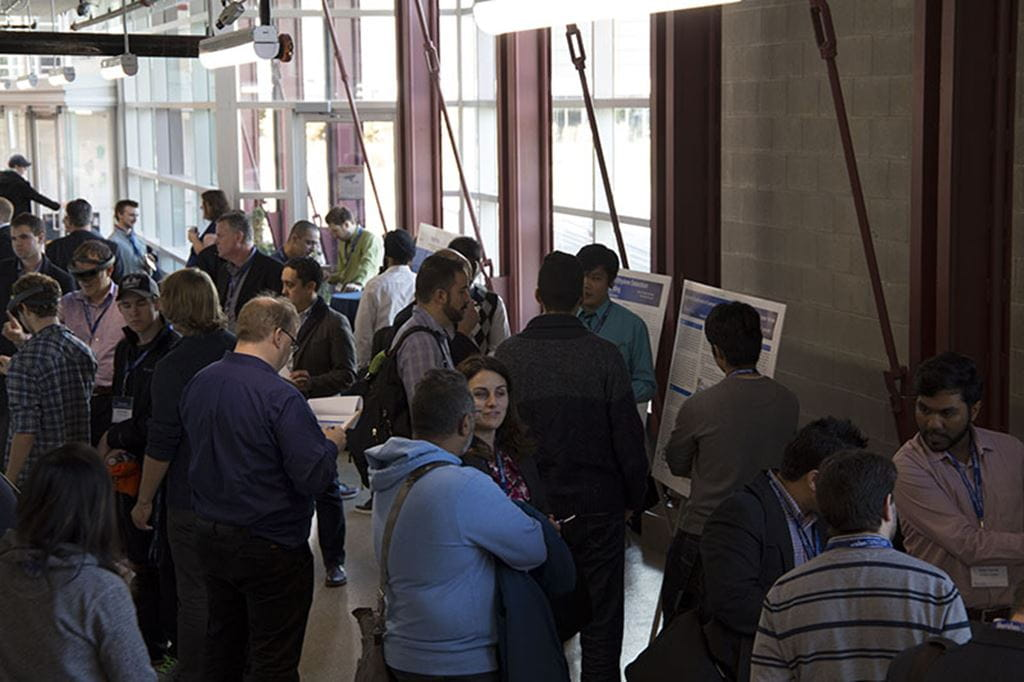 Event attendees take in the student poster competition held as part of the symposium