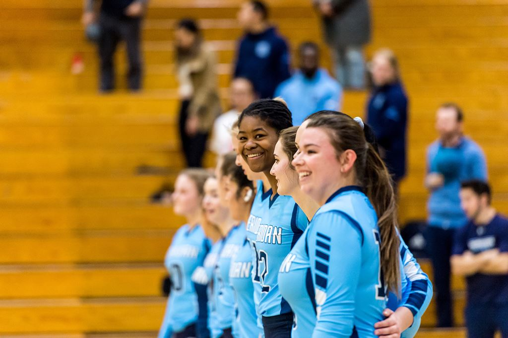 Sheridan Bruins volleyball players smiling on court