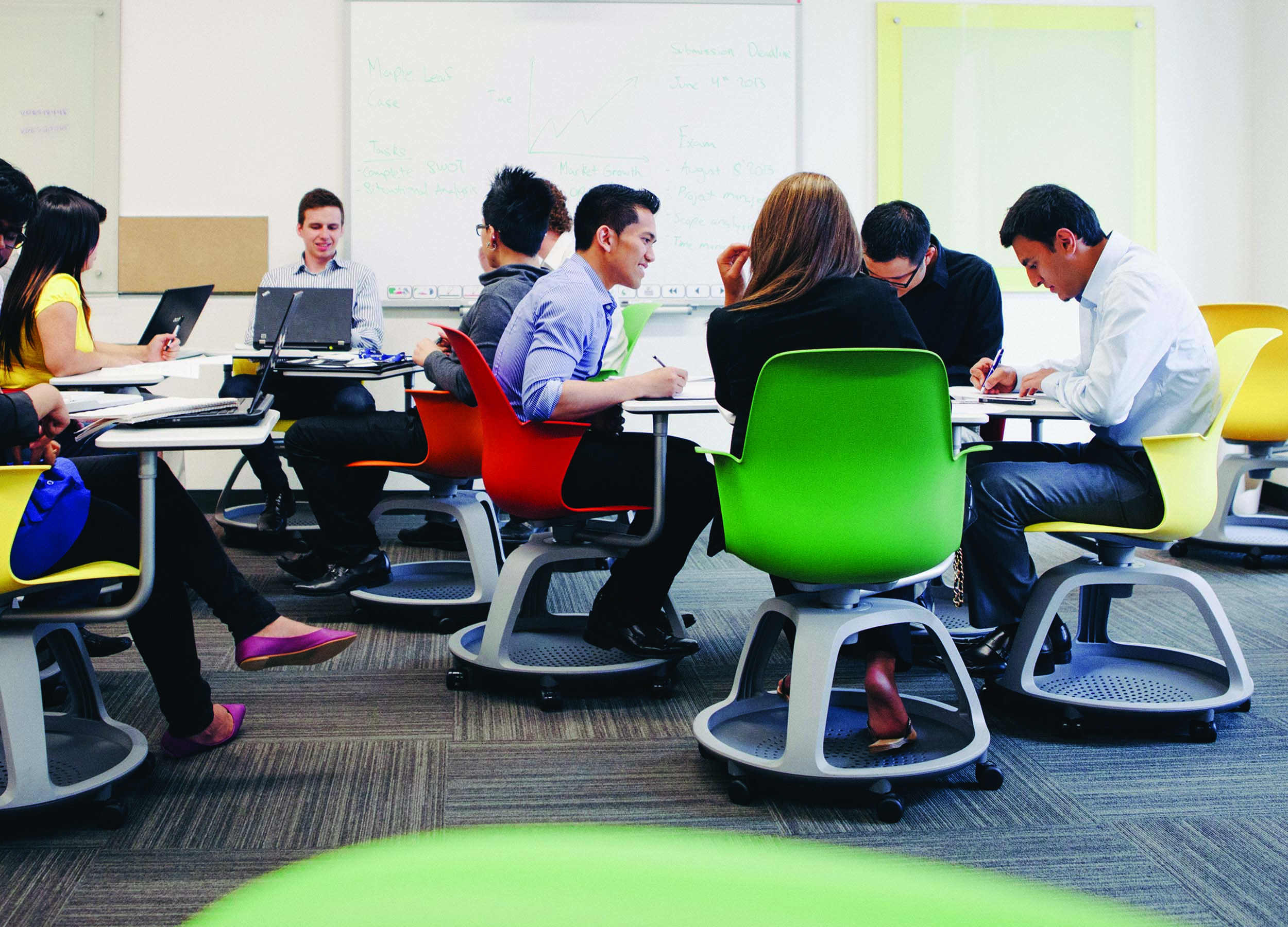 Students sitting in chairs around tables in a classroom