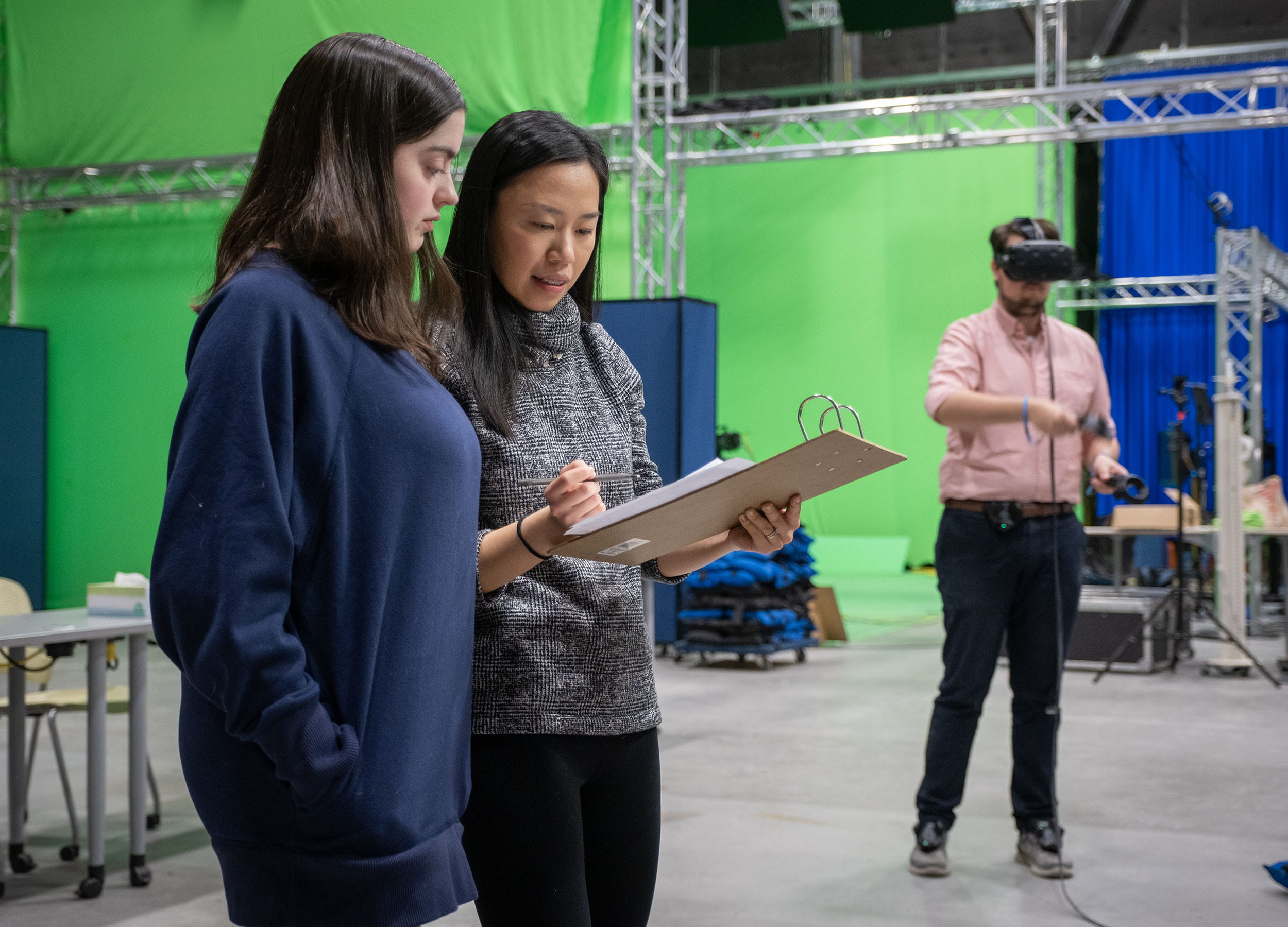 Two female students looking at a clipboard while a male student uses a VR headset