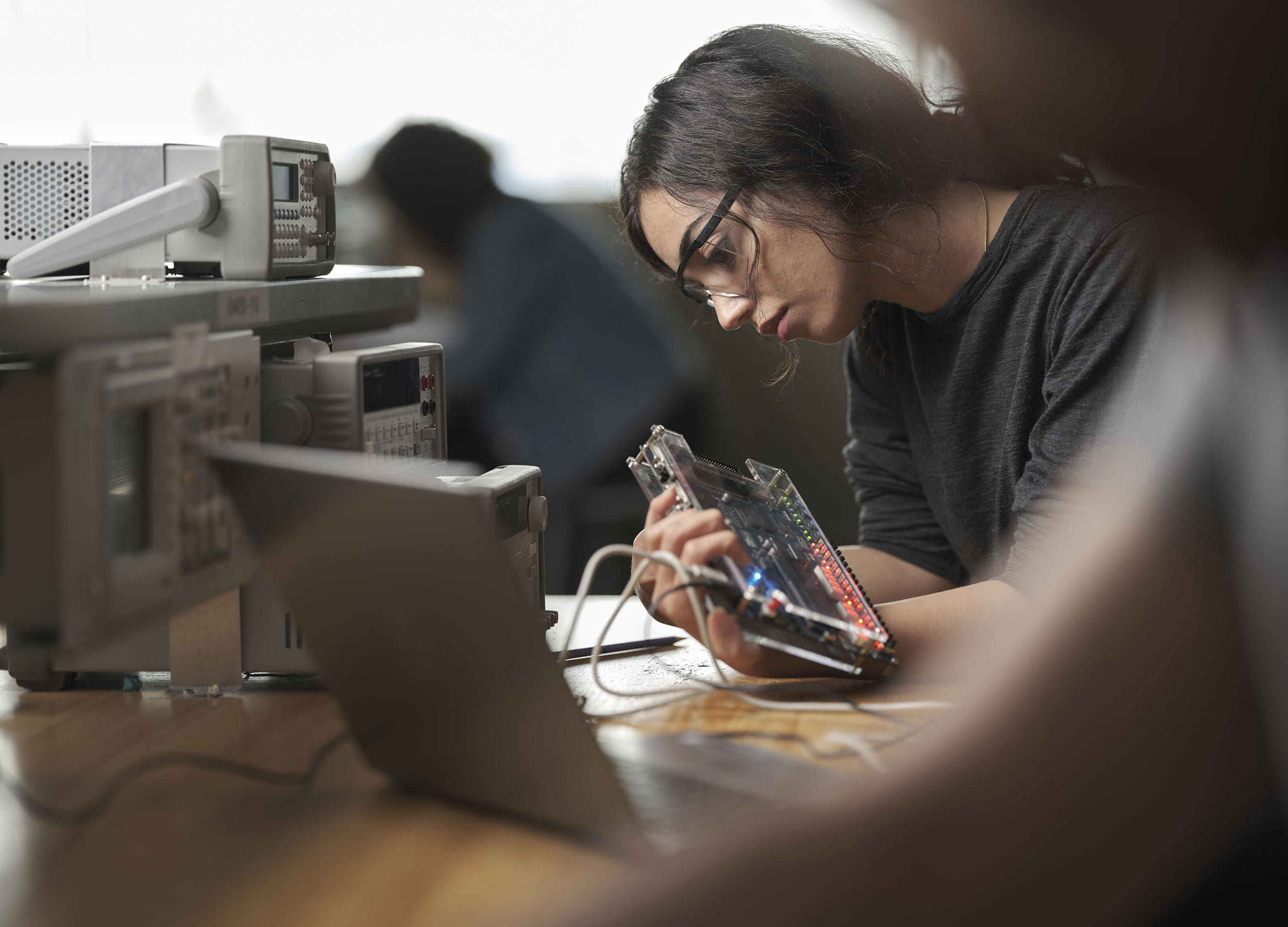 An electronics engineering technician student working in a lab