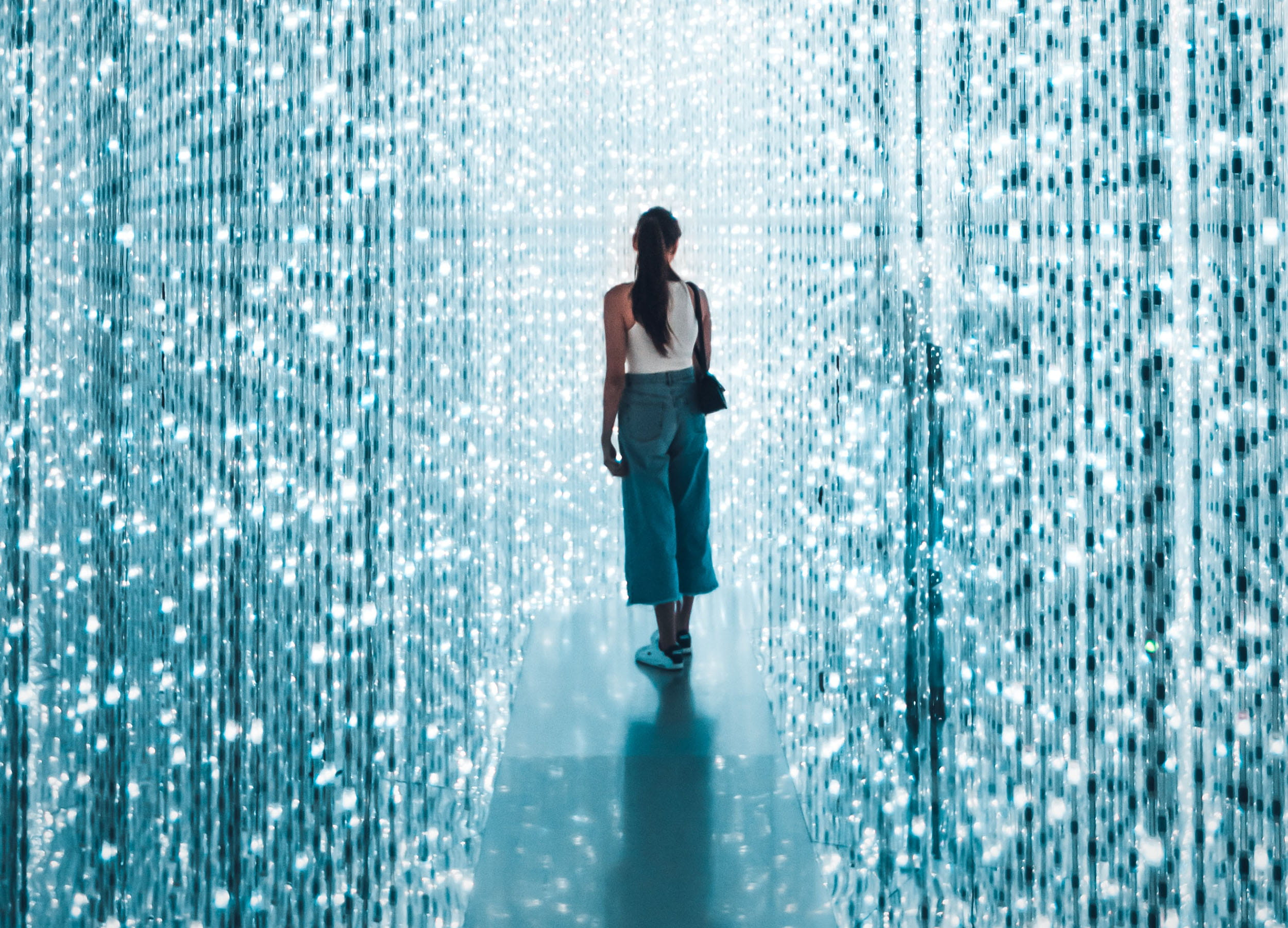 A woman standing on a small platform, surrounded by strings of blue and white lights running floor to ceiling.
