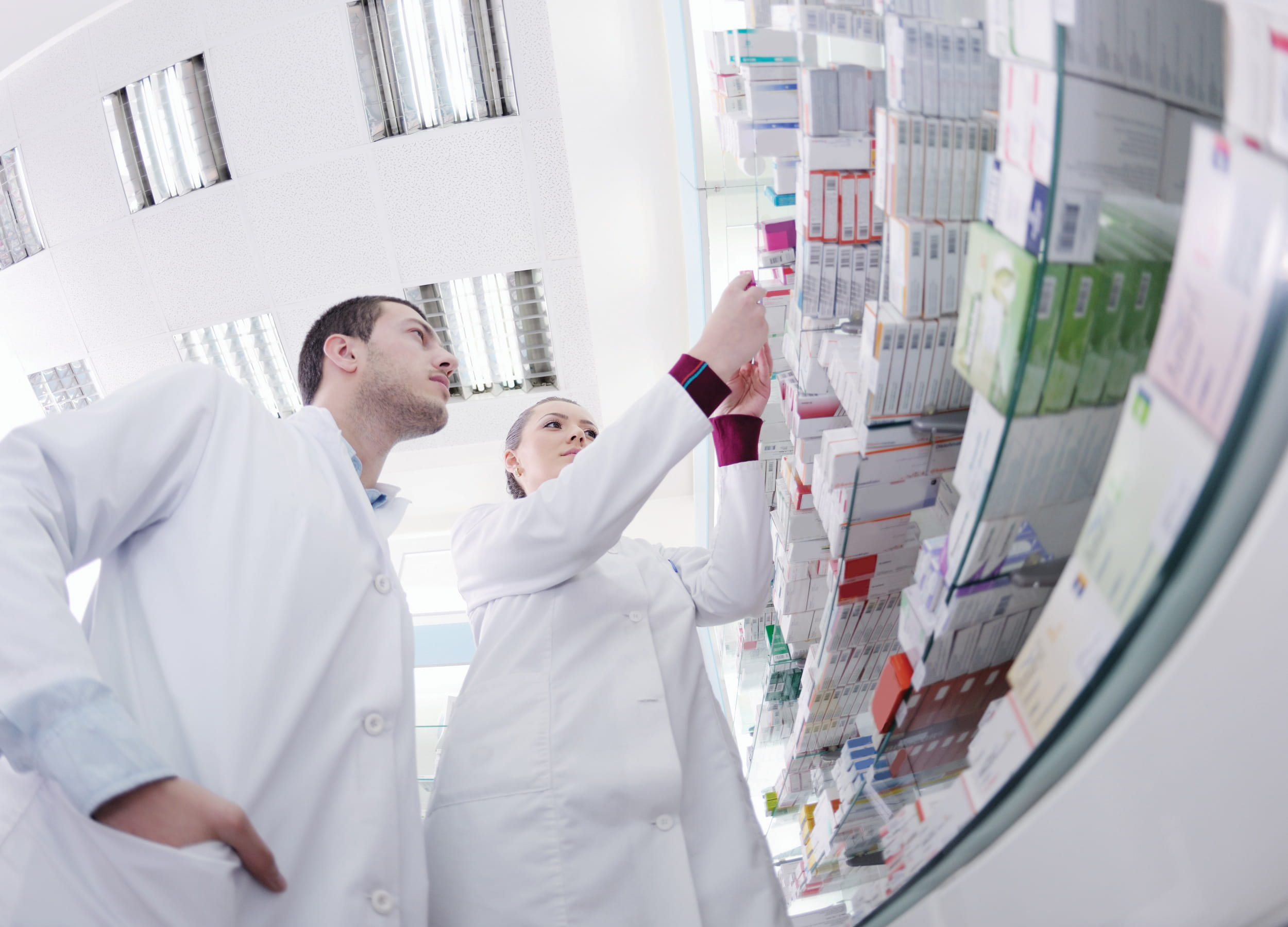 Pharmacy technicians looking at boxes of medication