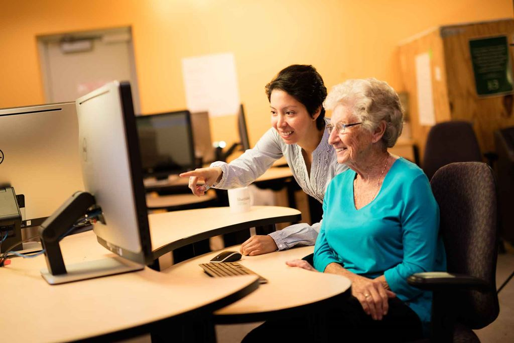 A young woman and an elderly woman looking at a computer together